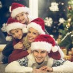 Happy family with two children with Santa hats lying down on the floor, looking at camera.